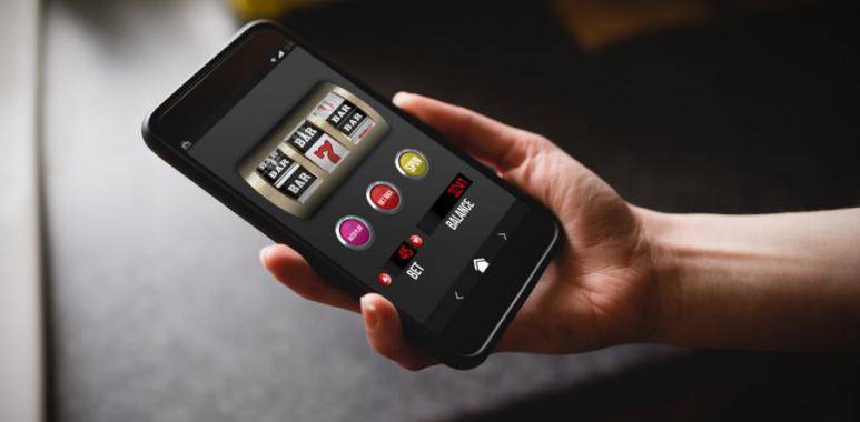 Händer som håller mobil och spelar slots med en papegoja som symbol